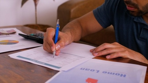 Close-up of man studying amount due for home loan payment due to bank