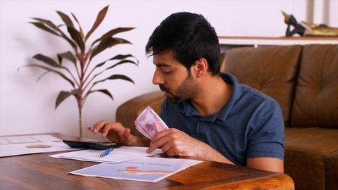 Young Indian man holding Indian currency Rs 2000 notes - Doing monthly budget expenditure calculations