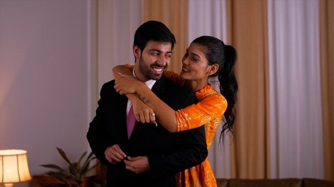 An attractive young Indian woman helps her husband to wear the blazer for the office - Office formal wear