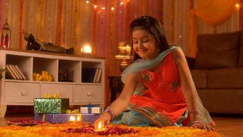 Diwali festival decoration - A cute happy girl decorating rangoli with Diya. Colorful house