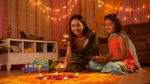 Beautiful and loving mother and daughter decorating flower's rangoli with Diyas - Festival