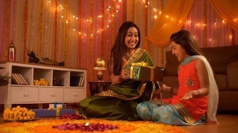 Indian Mother surprising her daughter with a Diwali gift - Sitting on the floor with a colorful decorated wall with lights and curtains