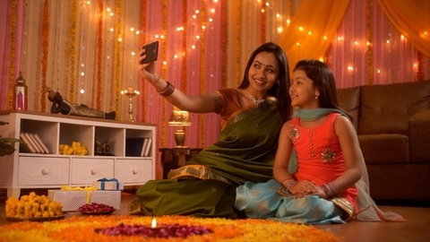 Festival occasion - young Indian mother is clicking a selfie with her daughter. Diwali decoration