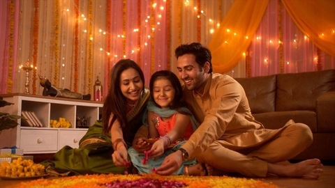 Diwali festival - An Indian nuclear happy family making Rangoli with flowers petal and loving their daughter