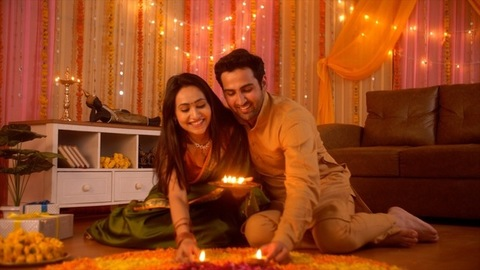 Diwali festival decoration - Young couple decorating rangoli with diyas. Colorful background with lights
