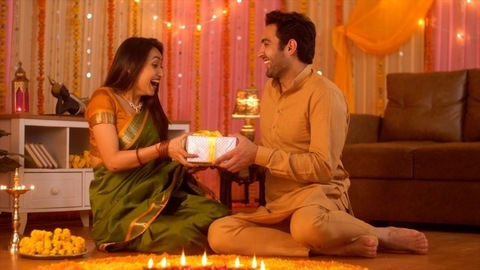 Diwali celebration - Handsome husband giving surprise gift to beautiful wife (Happy Indian Family)