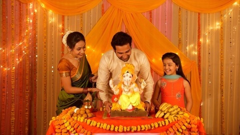 A nuclear Indian family setting up the Ganesha statue on the festival - Murti Sthapana
