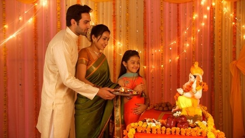 Beautiful Indian family worshiping Lord Ganesha during festivities - Puja and Aarti