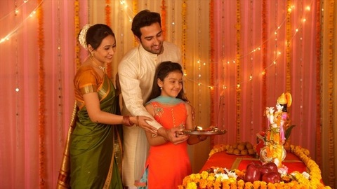 Indian Nuclear family worshiping Lord Krishna with Puja Thali - Love and care. Family bonding