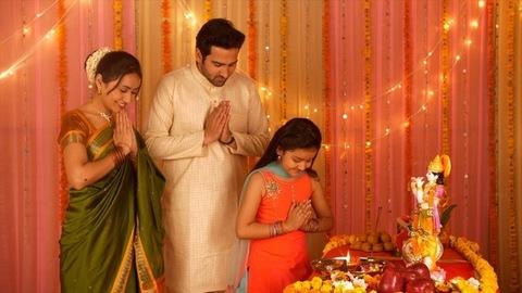 Happy Indian family celebrating Janamashtmi with love - Bowing with greeting pose