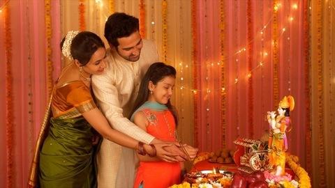 Nuclear Indian family celebrating Janamashtmi at home - Offering prayers to Lord Krishna