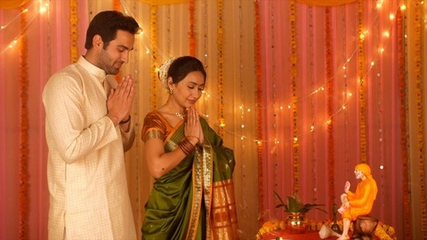 Indian married couple wearing ethnic clothes for Puja at home - Offering prayers to Sai Baba