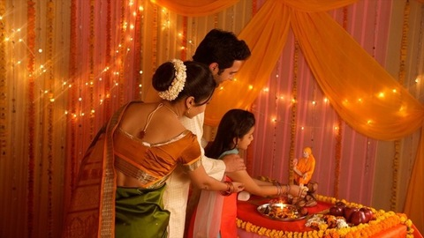 Indian nuclear family worshiping Indian Spiritual Master Sai Baba during festivities