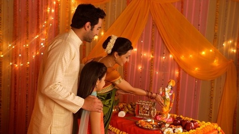 Nuclear Indian family offering flowers and bowing head in front of Hindu God