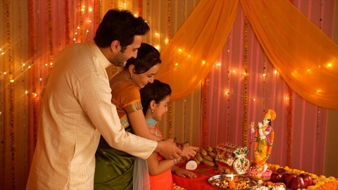 Happy Indian family performing Hindu rituals on the auspicious day of Janamashtmi