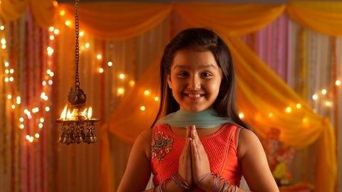 Indian girl with a smiling face looking at diyas - folding hands in namaskar position - Greeting pose