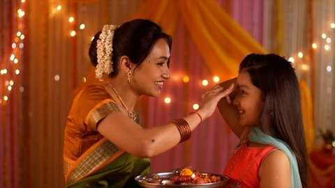 Mother putting tilak on young daughter's forehead - Celebration at home. Festive colorful background