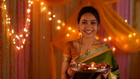 Beautiful Indian woman dressed in ethnic attire for festivities - Holding a puja thali and smiling towards the camera