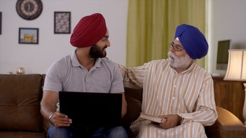 Sikh family scenario: Son showing his work to aged father on the laptop. Use of IT by senior citizen