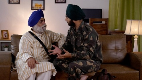 Indian soldier telling war stories to his retired father at home - Father-son spending quality family time