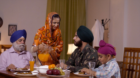 Beautiful young Sikh lady serving juice to her family members - family love. Indian army officer with his son, father, and wife