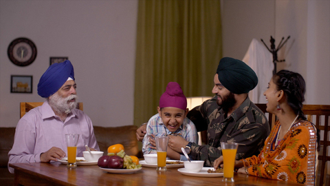 Happy Indian Sikh family - Father as Army officer. Fun time at the dining table during breakfast