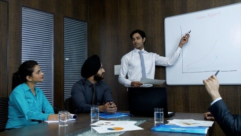 Indian manager presenting his monthly sales report to his senior colleagues - corporate office