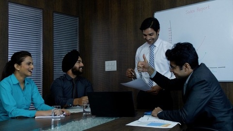 An ambitious and smiling boss with his employees. Appreciating his team for their achievements - Corporate office