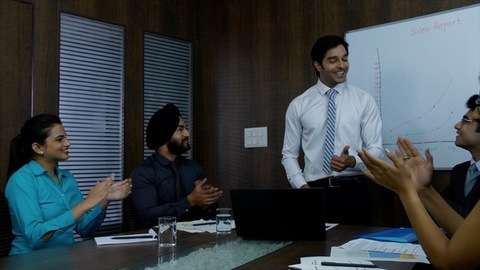Happy Indian manager showing their company growth report - Happy colleagues clapping and cheering