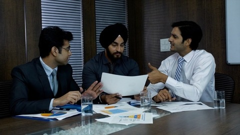 Happy Indian manager with his colleagues discussing project success - Corporate Office