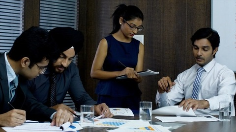 Indian manager having a meeting with his young employees in the conference room - Corporate Concept