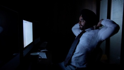 Tired businessman yawning while working late night in the office - Typing and making a business presentation
