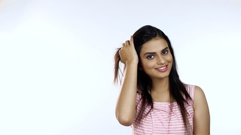 Beautiful Indian woman touching her hair and smiling - facing towards the camera