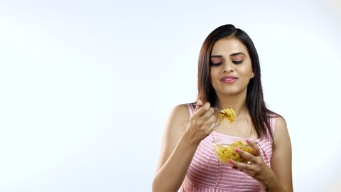 Indian beautiful girl eating noodles with pleasure in front of the camera - white background