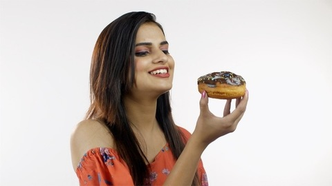 Beautiful Indian girl eating yummy chocolate donuts isolated over white background