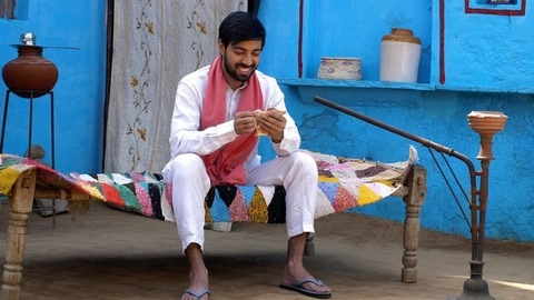 Happy Indian farmer calculating his last month's savings - future investment. Rural village life