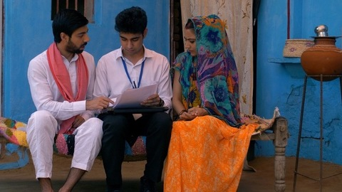 Bank agent helping Indian villagers to open new bank accounts - easy way to protect the money