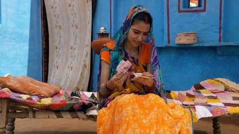 Happy Indian woman calculating her last month's savings - future investment. Village life