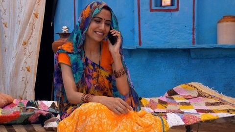 Indian lady happily talking on a phone with her relatives while sitting on a charpai - leisure time
