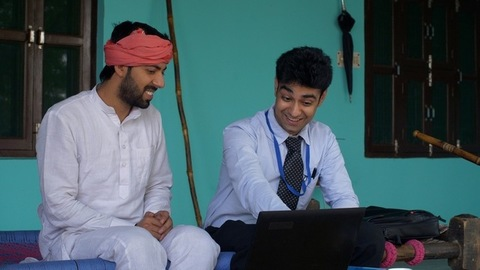 Young bank employee congratulating innocent Indian villager on his loan approval