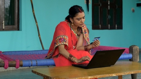 Young beautiful village woman doing card payment - online shopping concept. Rural life