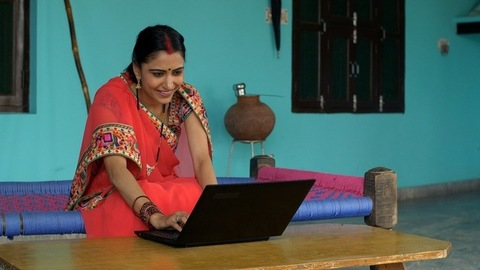 Happy Indian village lady using laptop and internet for the first time - rural households