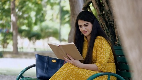 Attractive Indian girl happily reading a book/novel while sitting on a park's bench