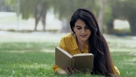 Young Indian woman reading a novel in her leisure time while lying in a garden