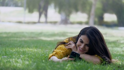 Beautiful Indian girl using her smartphone while lying in a garden - new technology