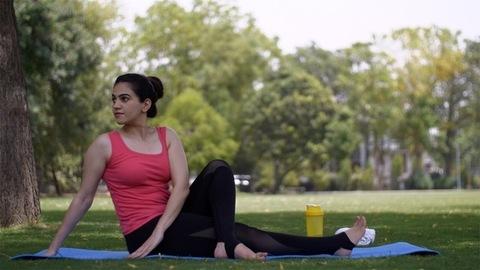 Healthy beautiful lady practicing Matsyendrasan Asana (half twist pose) on a yoga mat - sportswear