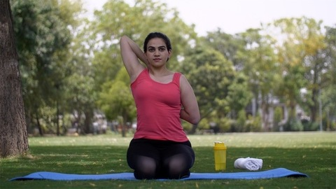 Young woman performing yoga exercises early morning in a garden