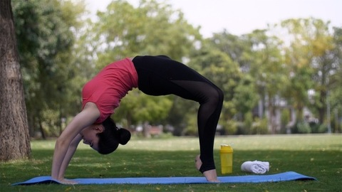 Pretty young lady practicing yoga on green grass with fitness mat in a park
