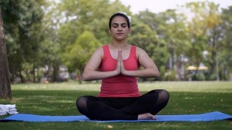 Young woman in athlete wear doing asanas while sitting on a yoga mat