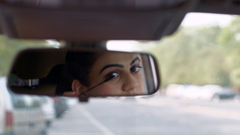 Indian business woman fixing her makeup in car parking before going to her workplace